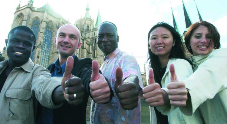 Eine Gruppe ausländischer Studierender stehen vor dem Dom in Erfurt, lächeln und zeigen den Daumen hoch